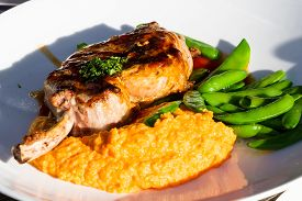 picture of sweet pea  - french cut pork chop served with a sweet potato puree and green peas on a white plate - JPG