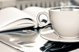 stock photo of office romance  - Cup of hot coffee and notepad on the desktop in the office.  Focus on the cup. Processing vintage black and white. - JPG