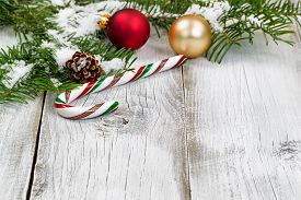 stock photo of candy cane border  - Candy cane with snow covered real Fir tree branches ornaments cone and snow on rustic white wooden boards. Christmas season concept. Focus on front part of candy cane.