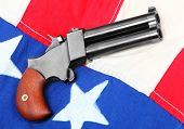 stock photo of derringer pistol  - Double derringer pistol on a american flag - JPG