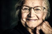 Portrait of a beautiful senior woman in elegant glasses smiling at camera.  poster