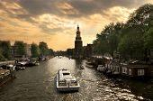 Постер, плакат: Вид на городской канал реки Амстел с круизный корабль в Амстердаме
