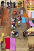 hindu men and women climbing the steep stairs to hindu temple on the ghats of varanasi