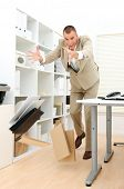Clumsy businessman dropping papers and files at the office