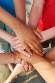 image of holding hands  - Hands of diverse group of teenagers joined in union - JPG