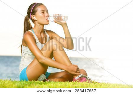 poster of Fitness woman drinking water after running training workout outside by ocean sea. Beautiful sweaty f