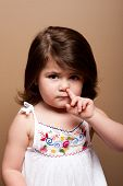 stock photo of snot  - Cute mischievous toddler girl with finger in her nose fishing for boogers snot on brown - JPG