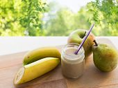 baby food, healthy eating and nutrition concept - glass jar with apple, pear and banana fruit puree  poster