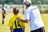 Back View Of Male Football Coach In White Coach Shirt At An Outdoor Sport Field Sending His Young Bo poster