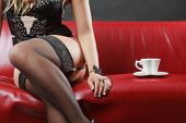 Erotic Fashion Concept. Sexy Lady Wearing Alluring Black Sensual Lingerie Sitting On The Couch Havin poster