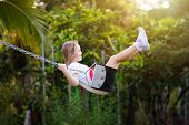 Child Swinging On Playground. Kids Swing. poster