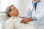 Mature Doctor And Senior Patient In Hospital Ward. poster