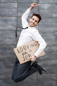 stock photo of unemployed people  - Young man jumping with a Looking for a job sign - JPG