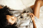 stock photo of mixed race  - Young african woman with cat indoors - JPG