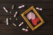 Flat Lay Romantic Background. Giftbox, Rolled Wish Papers, And Wooden Frame With Paper Hearts On Dar poster