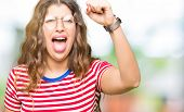 Young beautiful woman wearing glasses angry and mad raising fist frustrated and furious while shouti poster