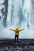 A Person Admirnig The Beauty Of Skogafoss Waterfall Located In Iceland poster