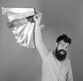 Man With Beard And Mustache Holds Shopping Bags, Red Background. Guy Shopping On Sales Season With D poster
