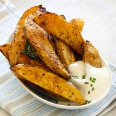 Spicy potato wedges in small bowl with sour cream.