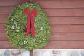 stock photo of fieldstone-wall  - A Christmas evergreen wreath with a red bow on the side of a log and fieldstone cabin wall - JPG