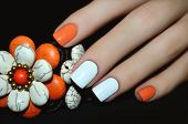 Female Hand With Orange Nail Design Holding Bracelet poster