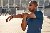 Preparing For Workout. Close Up Portrait Of African Athlete Stretching His Arms During Morning Worko poster