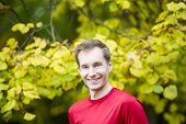 stock photo of stressless  - Male runner in an autumn forest with a water bottle - JPG