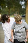 stock photo of physical therapist  - physical therapist helping a woman on crutches - JPG