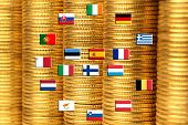 Flags Of Eurozone Countries Against Piles Of Coins