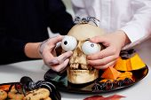 stock photo of eye-sockets  - Photo of two boys hands holding spooky eyes just in skull eye - JPG