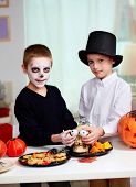 stock photo of eye-sockets  - Photo of twin boys holding spooky eyes just in skull eye - JPG