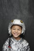 Portrait of a cute young boy in aluminum foil astronaut costume smiling against black background