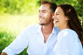 Happy Couple Outdoor. Smiling Couple Relaxing in a Park. Family over Nature Green Background. Smilin