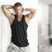 image of hot pants  - Portrait of sexy muscle man posing in modern studio - JPG