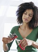 picture of overspending  - Young mixed race woman cutting credit card against white background - JPG