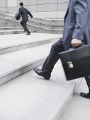 pic of late 20s  - Side view of a businessman running on stairs with cropped man in foreground - JPG