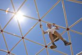 stock photo of pre-teen boy  - boy playing on high up on playground - JPG