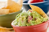 Guacamole and Chips - A studio shot of homemade guacamole in a red bowl., tortilla chips in a green