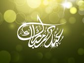 Arabic Islamic calligraphy of text Eid Mubarak on shiny abstract green background.
