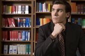 foto of shelving unit  - Thoughtful young man in formals in the library - JPG
