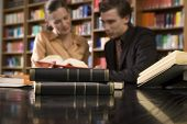 stock photo of shelving unit  - Blurred young man and woman studying at desk in library with focus on books in foreground - JPG