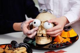 stock photo of eye-sockets  - Photo of two boys hands holding spooky eyes just in skull eye - JPG
