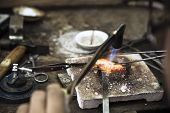 foto of arts crafts  - Close up of Jeweler crafting golden rings with flame torch - JPG