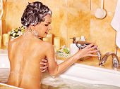 picture of bath sponge  - Young woman using bath sponge in bathtub - JPG