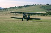 stock photo of biplane  - A vintage camouflage biplane secured to the ground at a grassy airfield - JPG