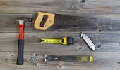 image of pry  - Top view of basic home repair tools consisting of wood saw hammer nails box cutter pry bar and tape measure on rustic wooden boards - JPG