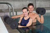stock photo of day care center  - Happy couple working out with foam dumbbells in swimming pool at the leisure centre - JPG