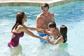 pic of swimming pool family  - A mother and father having fun on vacation playing with their children on their shoulders in a swimming pool - JPG