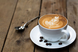 stock photo of liquid  - Cup of hot latte art coffee on wooden table - JPG