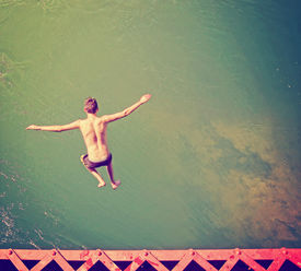 image of trestle bridge  -  a boy jumping of an old train trestle bridge into a river done  - JPG
